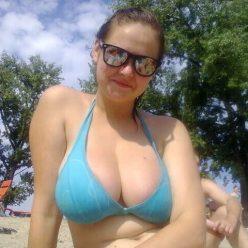 Фото девушка с большой грудью в купальнике и очках на пляже